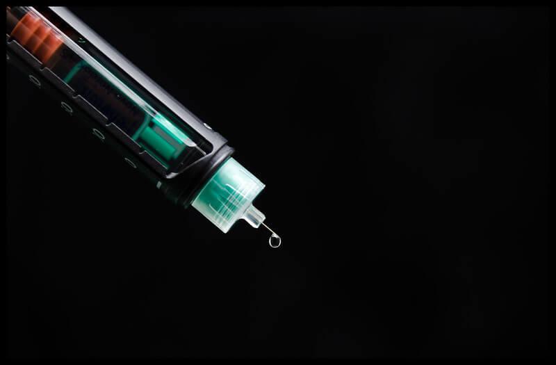 Photo og an insulin syringe against black background