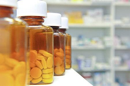Bottles of medicine lined up with pills inside