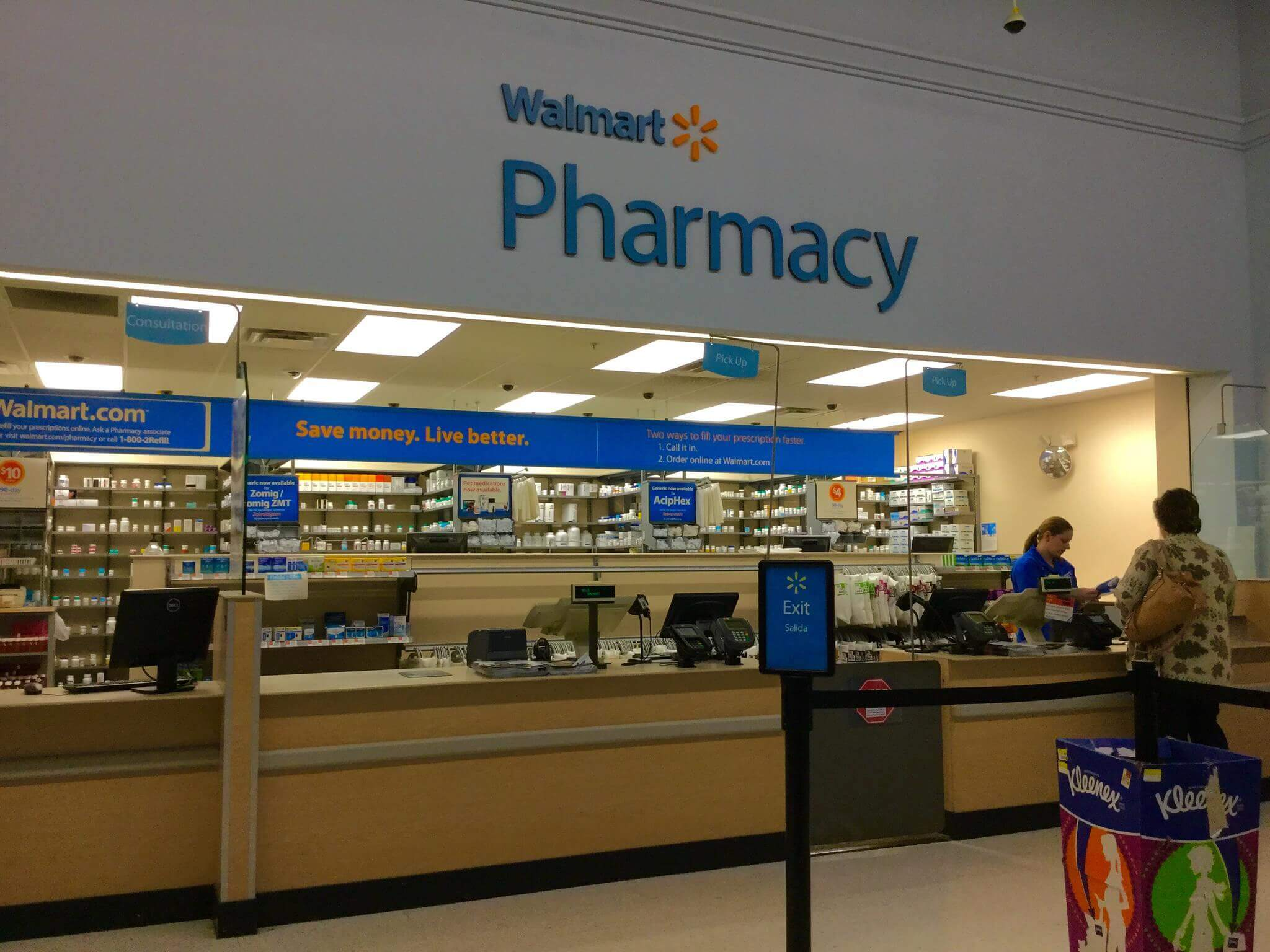 Photo of Walmart pharmacy with a cashier inside and a customer
