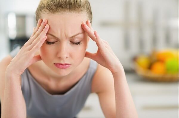 Woman touching her temples due to migraine