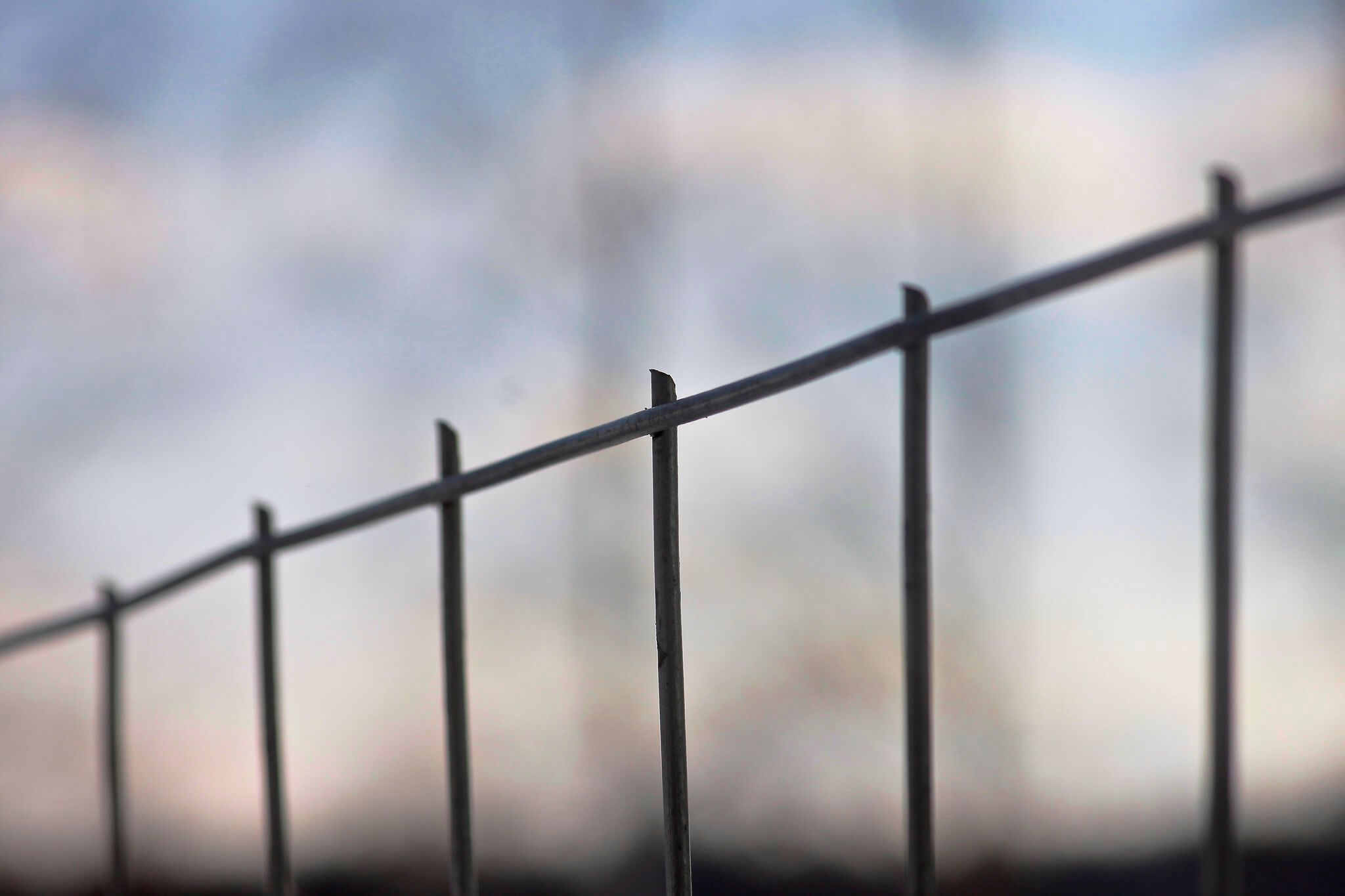 Photo of a prison fence against the clouds