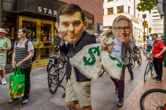 Street protest with Shkreli's mask held by a protester