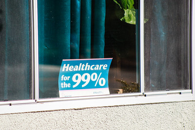 Sign on a window that says 'healthcare for the 99%'