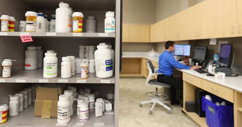 Photo of medicine bottles on shelf with a pharmaceutical staff working on the side