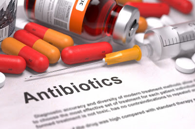 Antibiotics on top of documents with the word antibiotic written on it