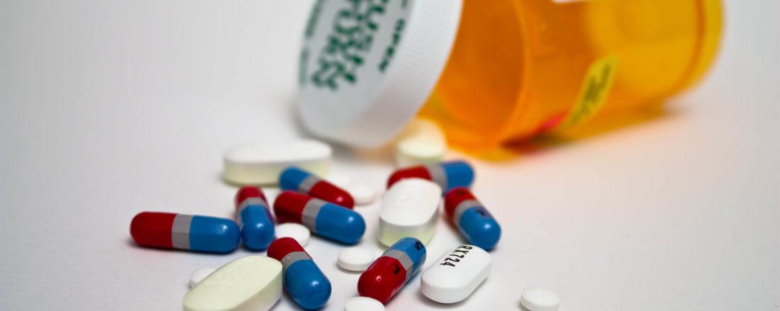 Multi-colored pills spilled outside medicine bottle