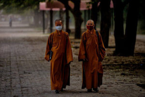 Monks walking in the park wearing masks