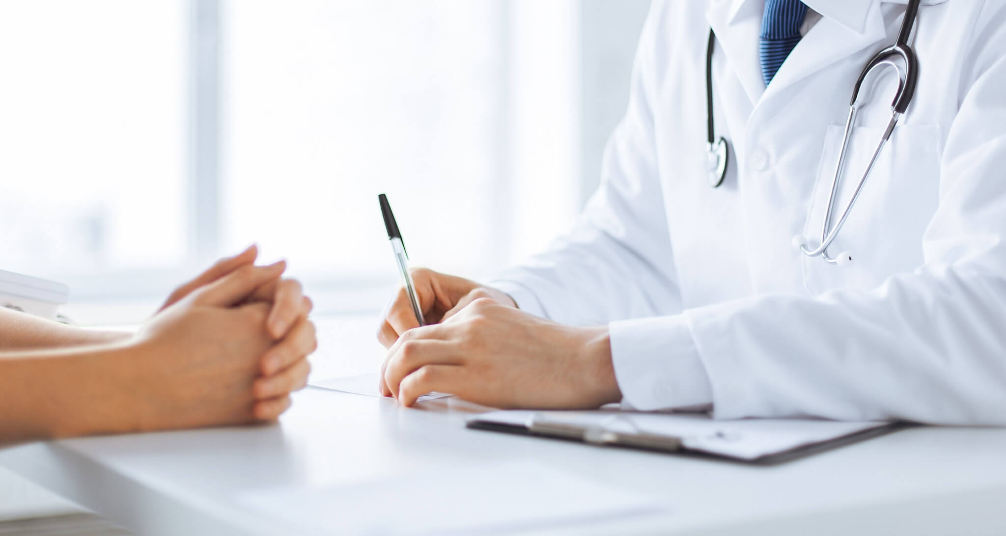 Doctor taking notes while talking to patient