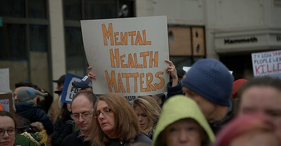 Person holding a sign saying 'mental health matters'