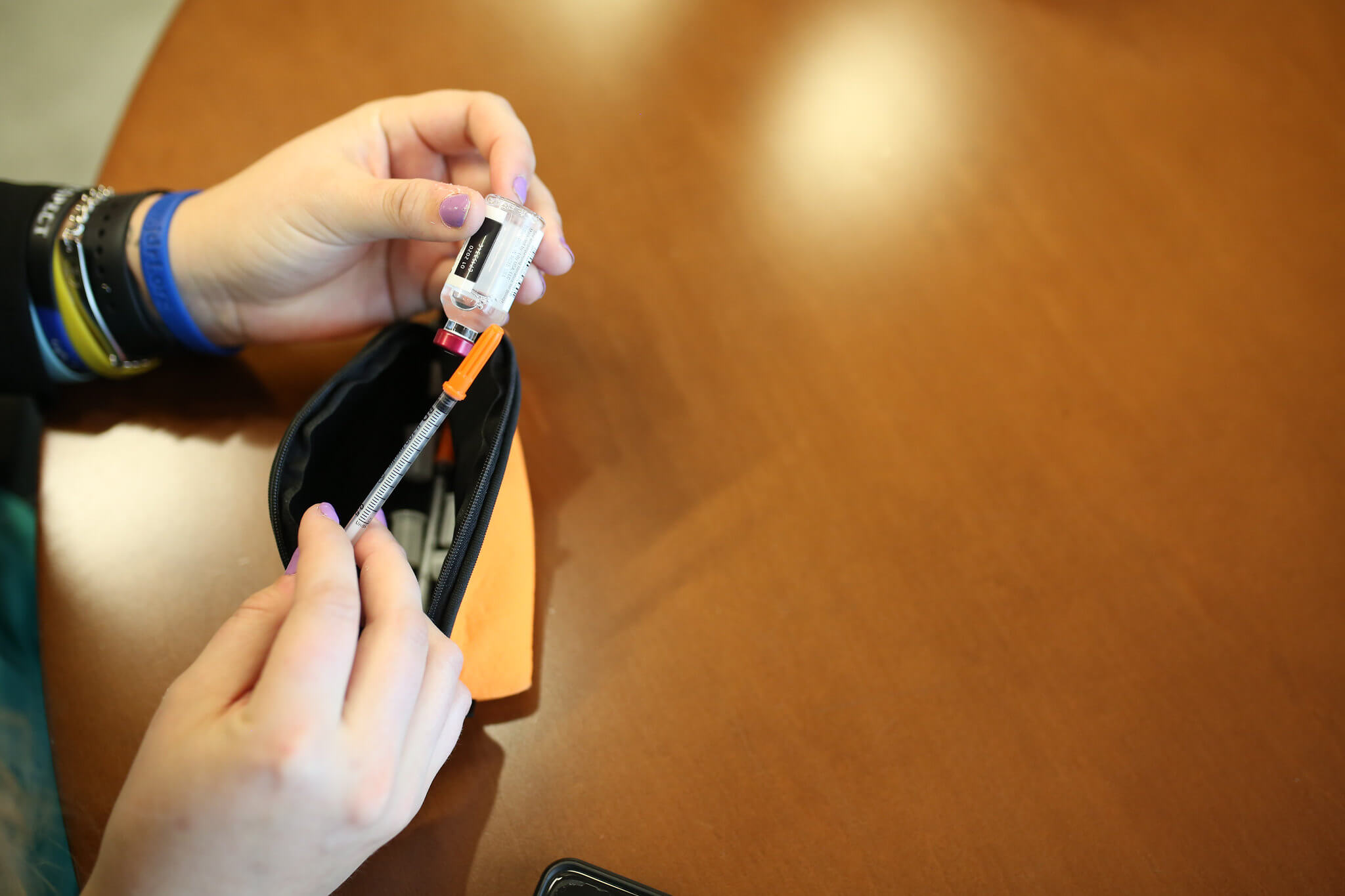 Person holding an insulin and syringe while on table