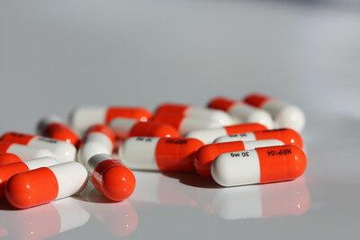 Orange pills spilled on a white floor