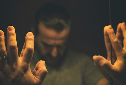 Man with his hands leaning on the mirror