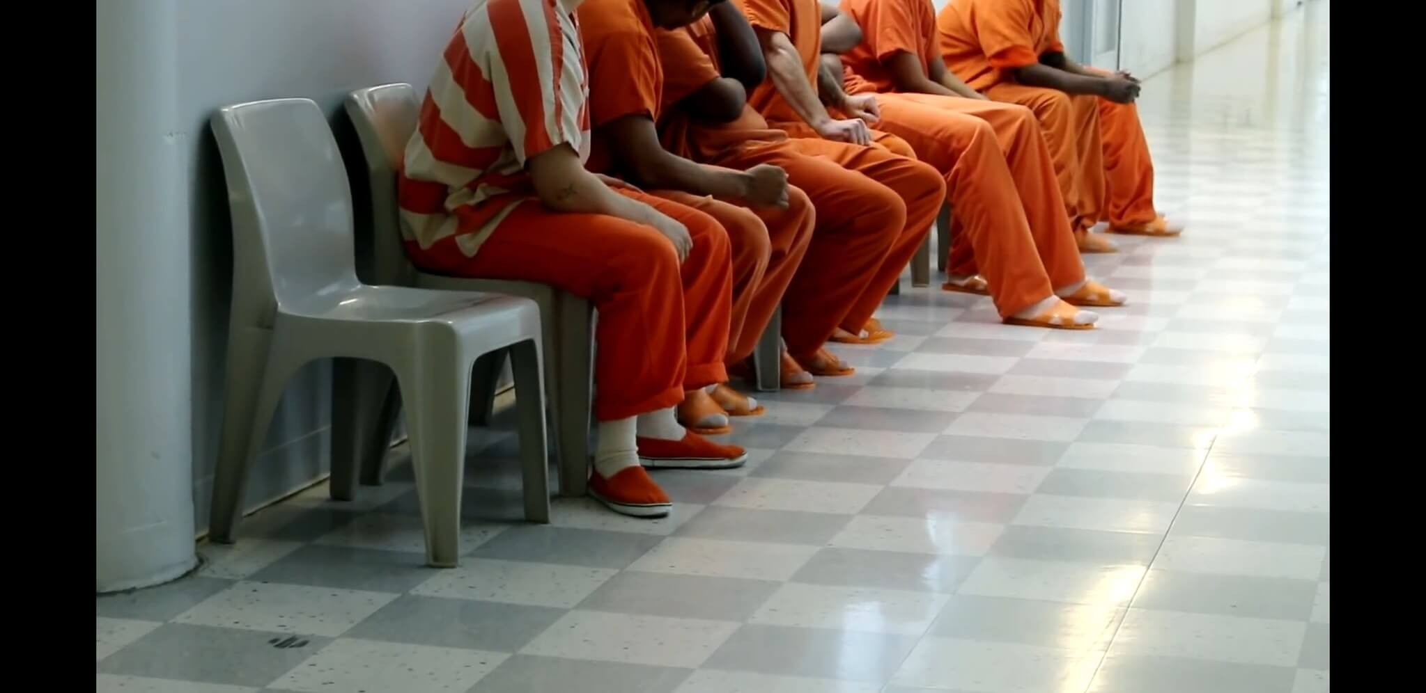 Prisoners in orange seated next to each other