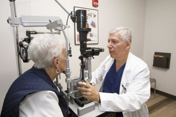 An ophthalmologist checking the eye of an elderly woman