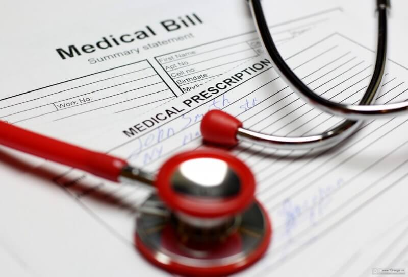 Red stethoscope on top of medical bills and medical prescription