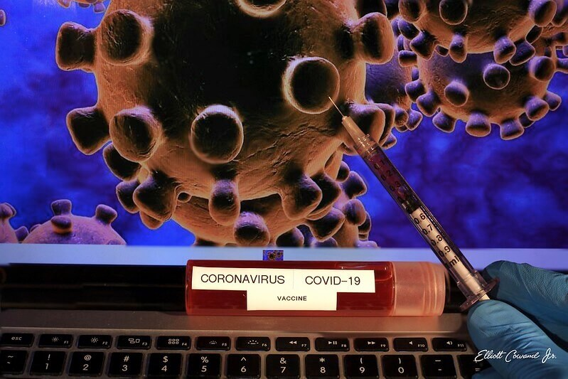 "Picture of a virus on a laptop with a syringe pointed to it and a vial labeled ""coronavirus vaccine"" below it"