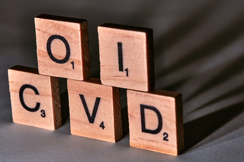 Photo of COVID letters in scrabble casting a shadow on its back