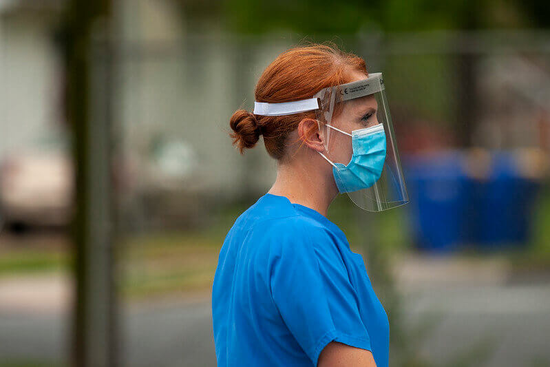 Woman walking on American streets wearing a mask and a face shield