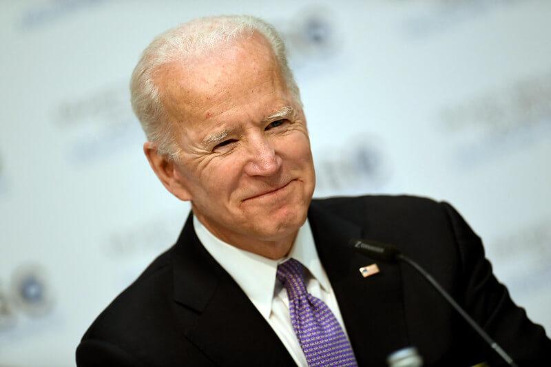 Joe Biden smiling while delivering a speech