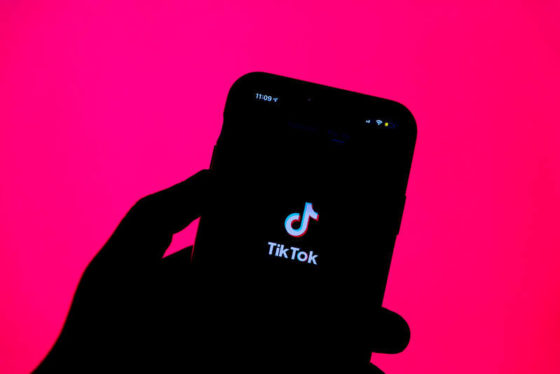 Silhouette of a person holding a phone with the TikTok app logo in it
