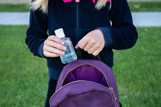 Young girl putting a hand sanitizer inside her bag
