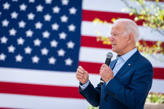 Joe Biden having his speech with the American flag at the background