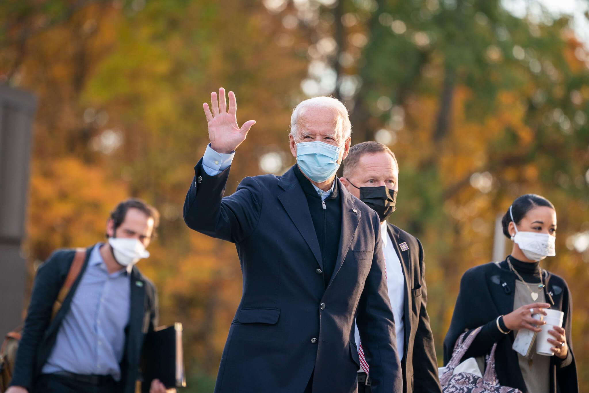 Joe Biden wearing a mask while waving to people