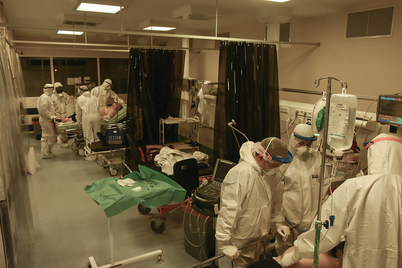 Hospital room filled with medical staff wearing PPE tending to patients