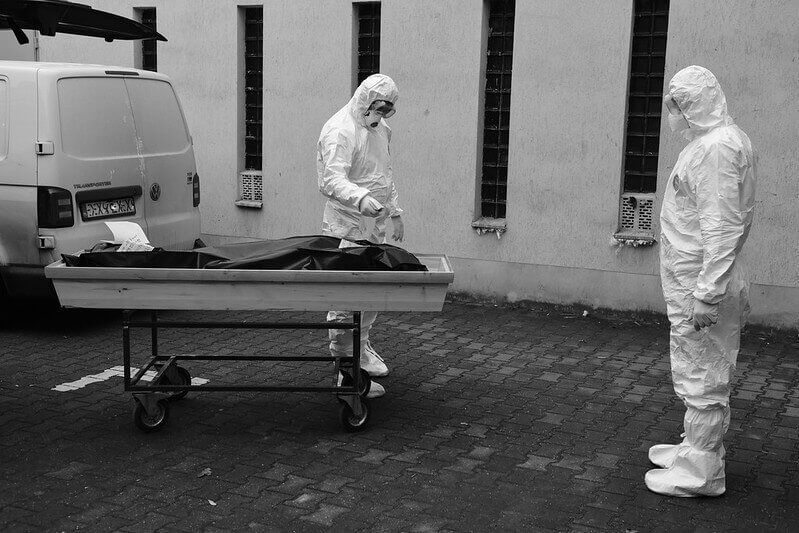 Photo of two health care staff transporting a dead body