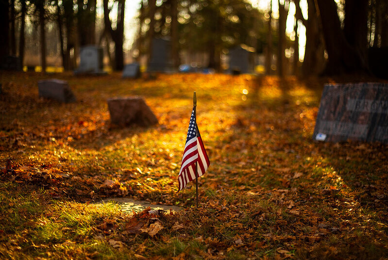 Photo of the American flag on a stick planted in the soil