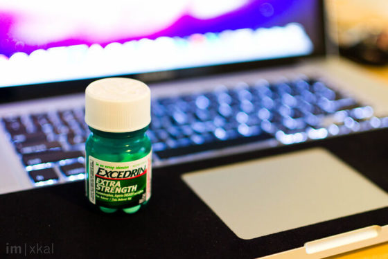 Photo of Excedrin Extra Strength medicine bottle in front of a laptop