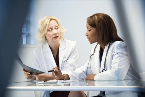 Two female doctors talking while looking at documents