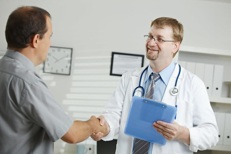 A doctor and a patient greeting each other with a handshake