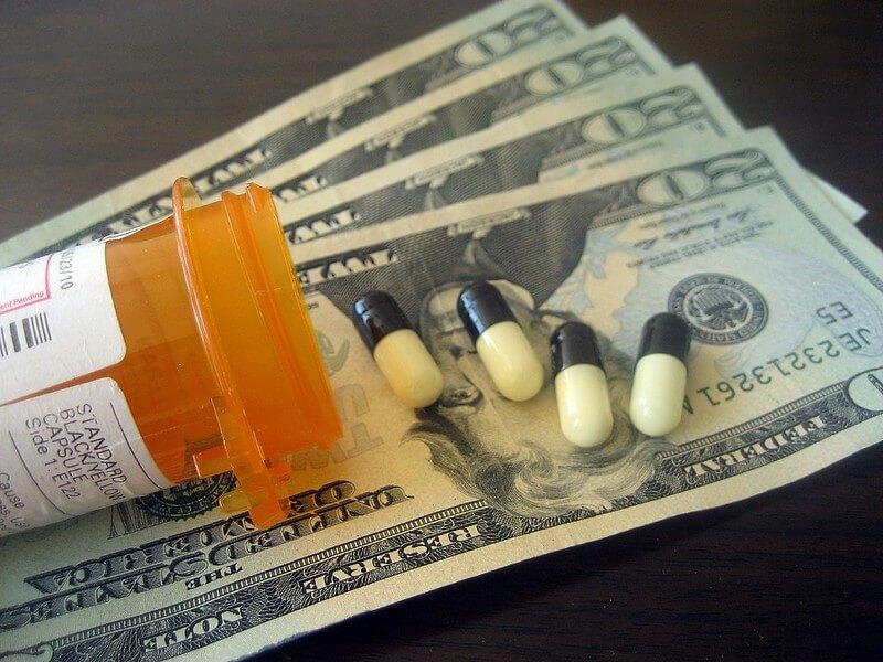 Scattered medicines on top of dollar bills
