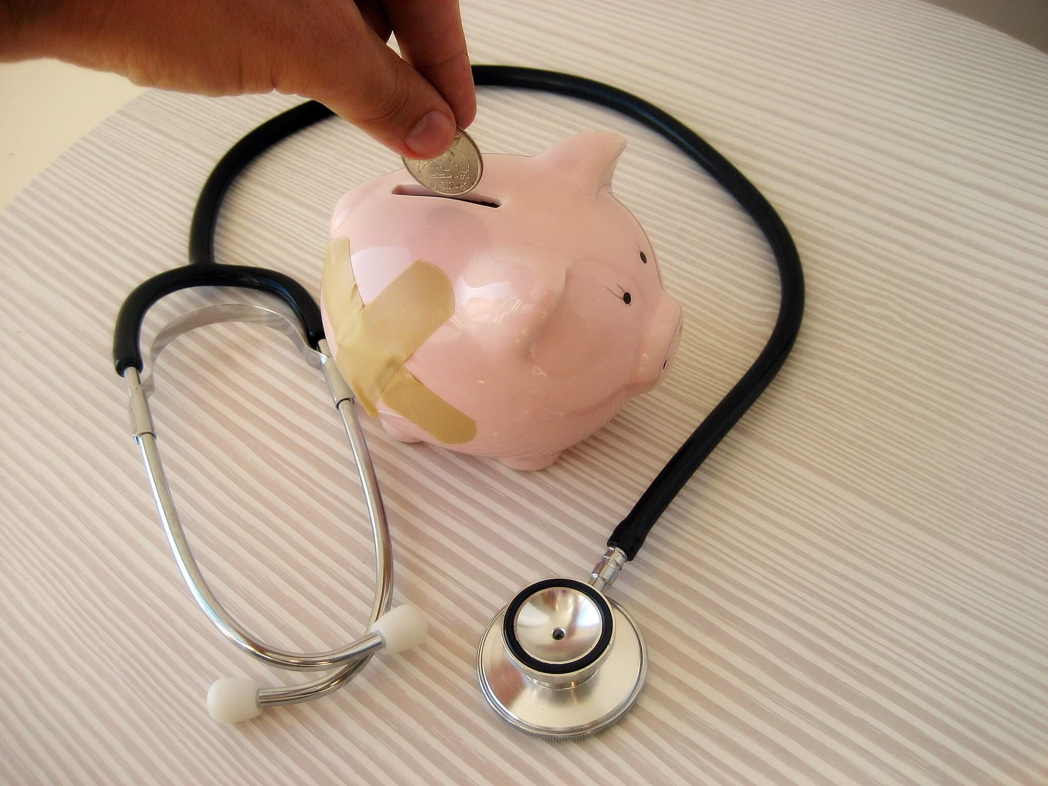 Piggy bank with band aid and a stethoscope around it