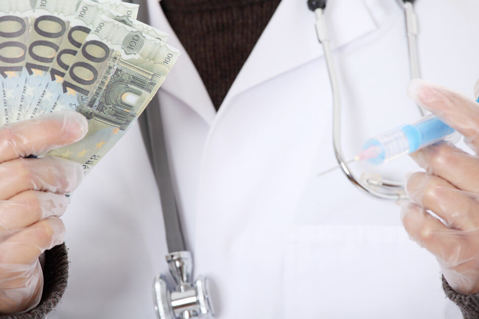 Doctor wearing a coat while holding syringe and dollar bills