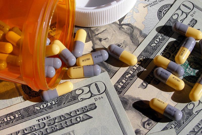 Pills spilled outside of bottle on top of dollar bills