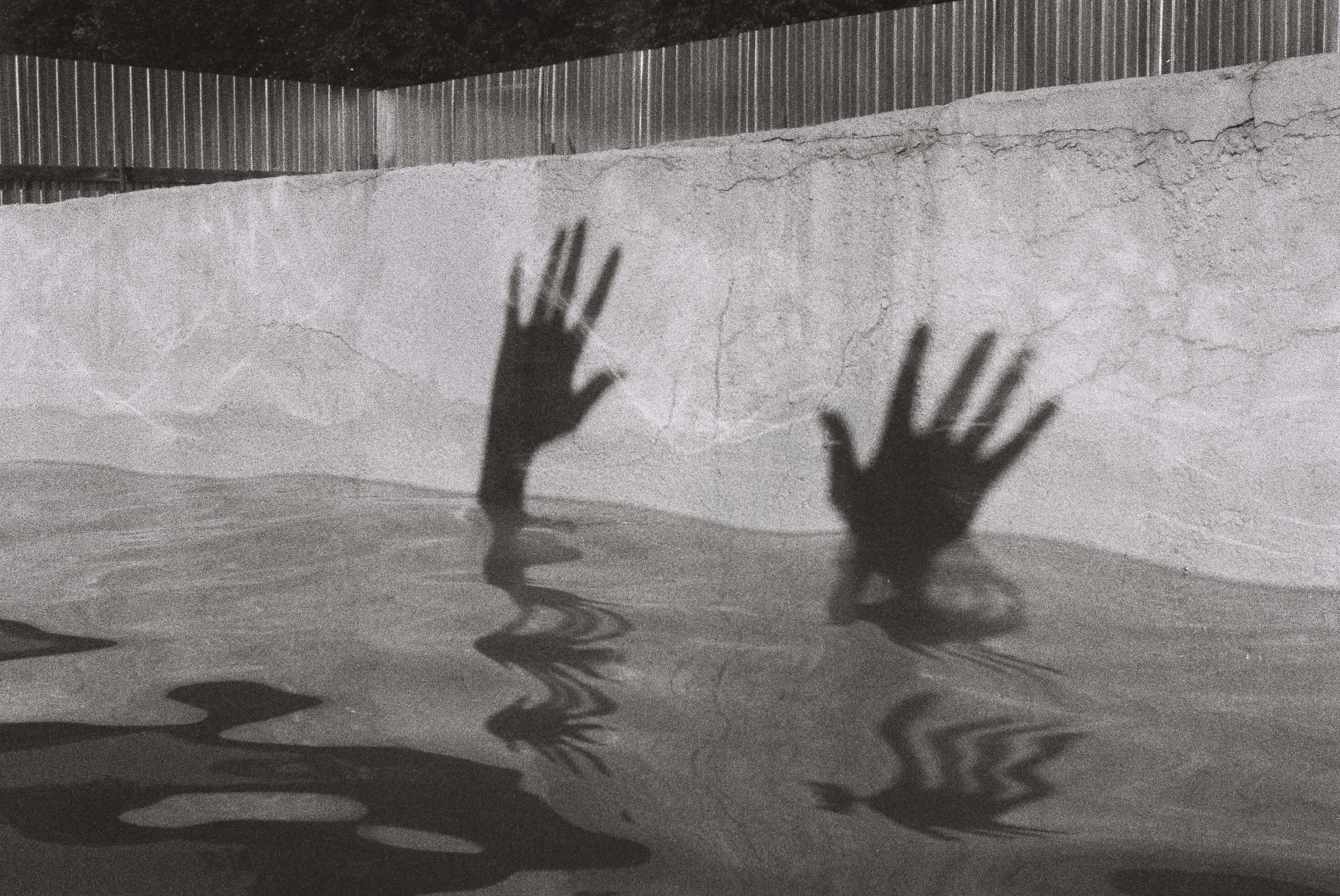 Silhouette of hands on top of water