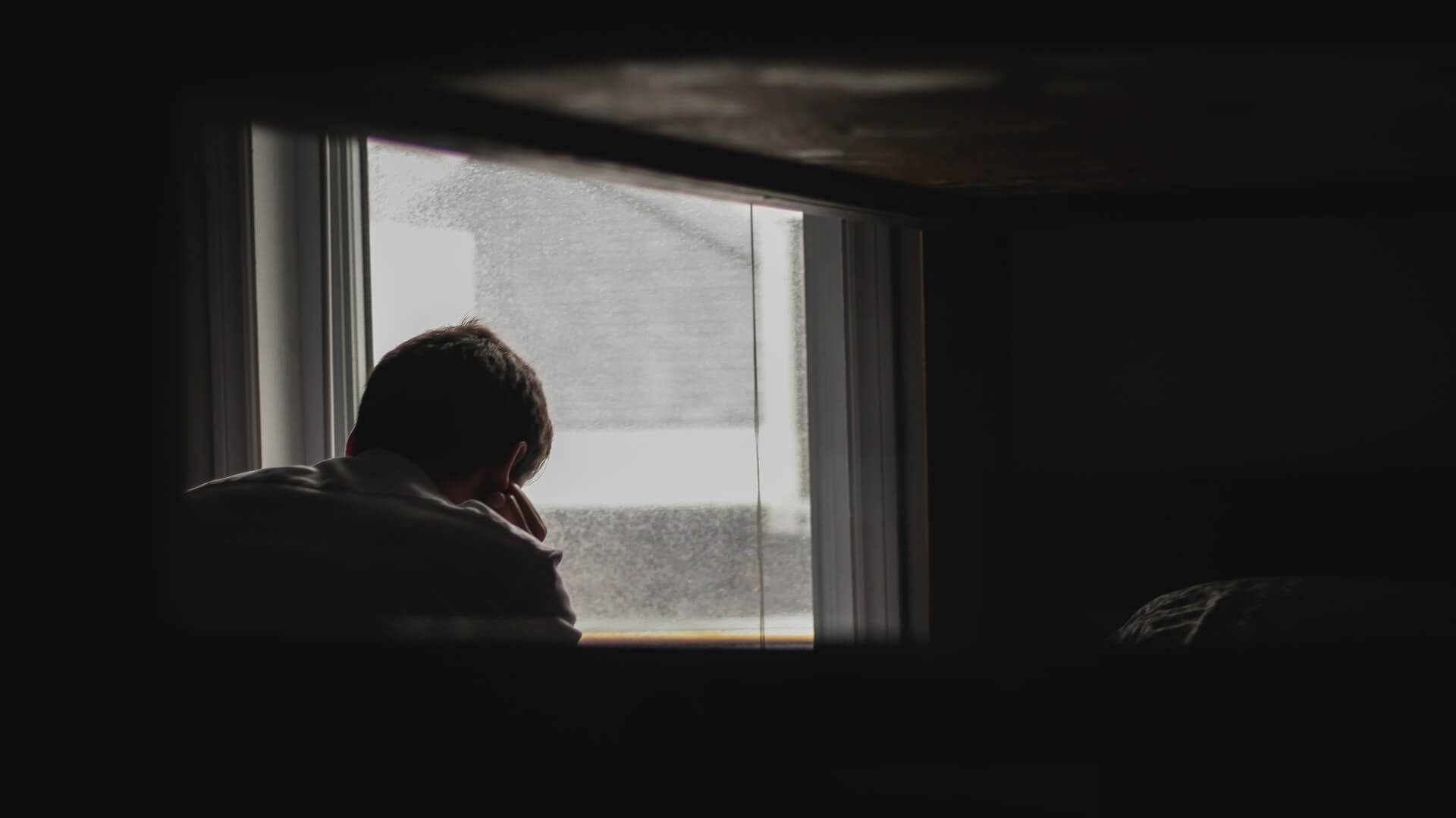 Man holding his forehead while staring at the window