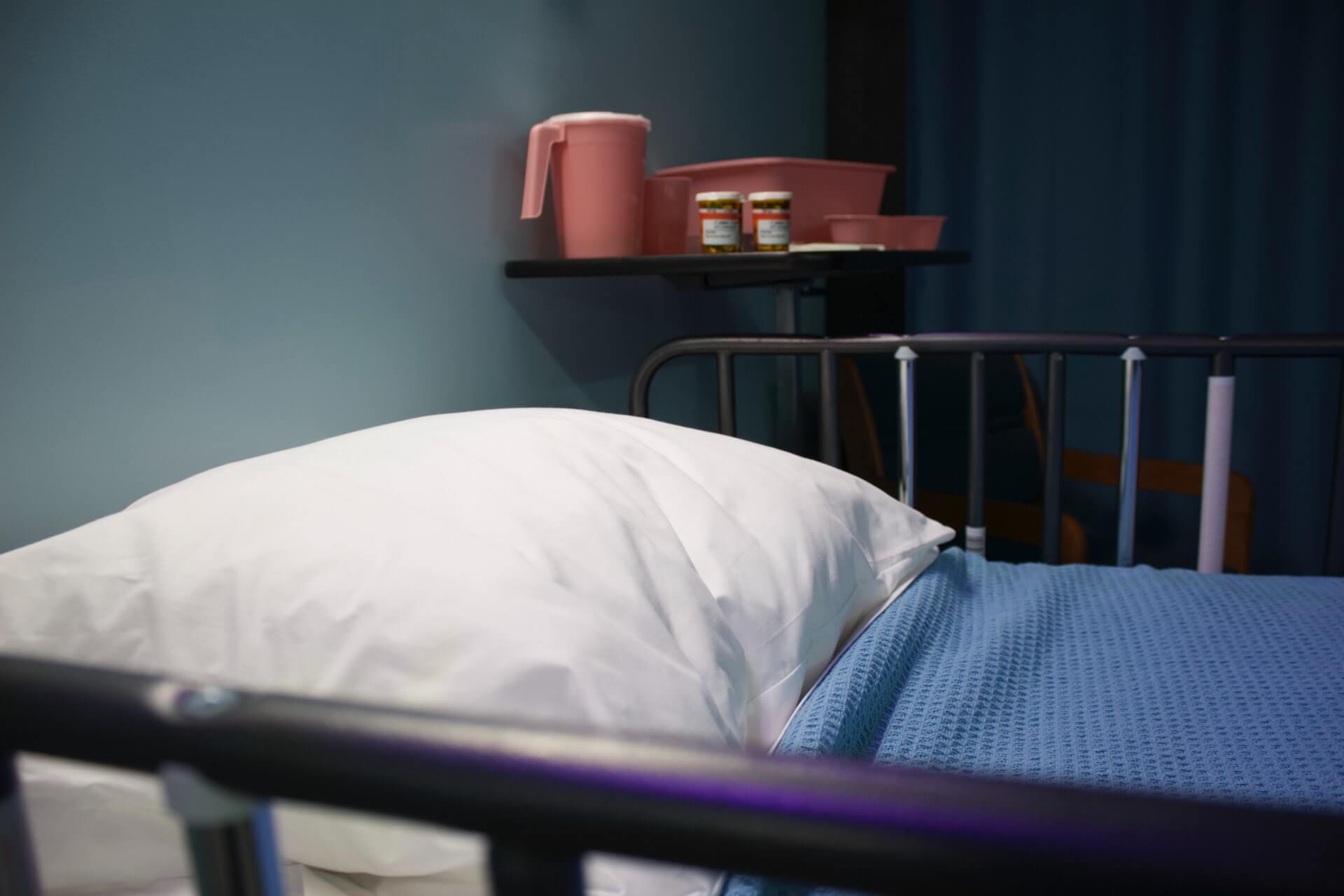 Hospital bed with medicine bottles on side table