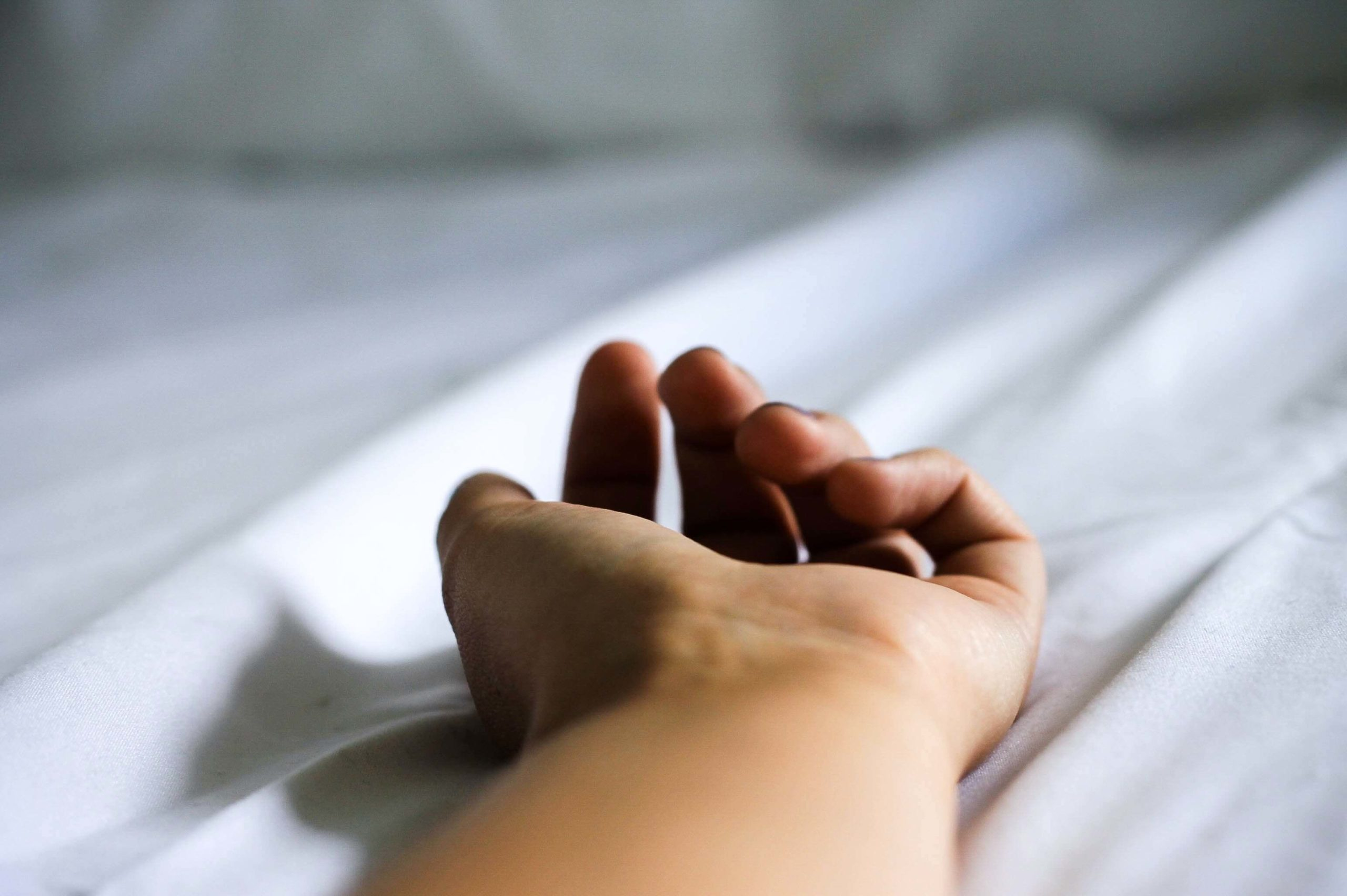 Hand on top of white bed sheet