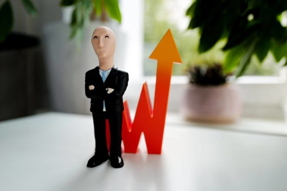 Male doll standing in front of line graph