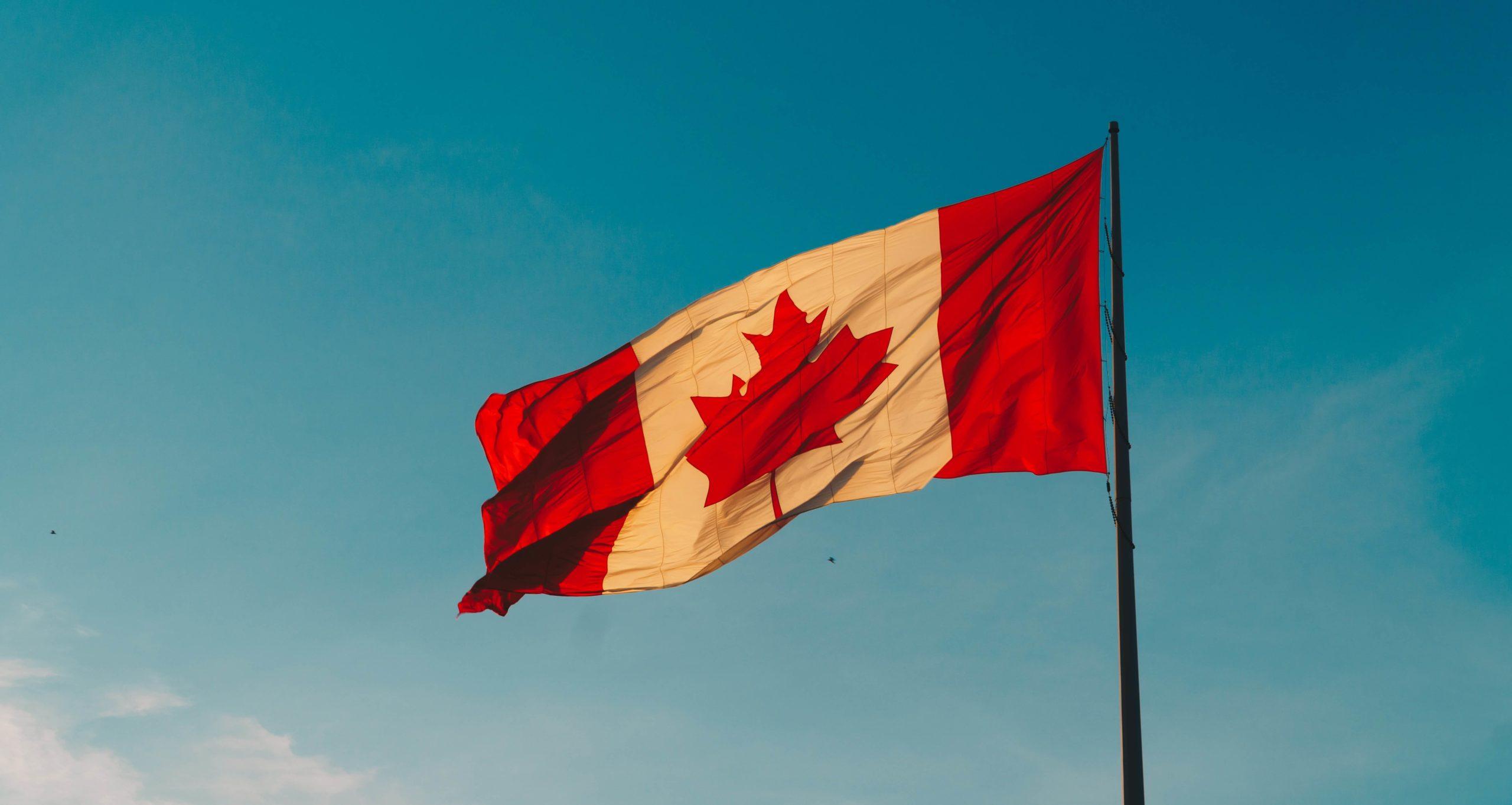 Canadian flag against the blue sky