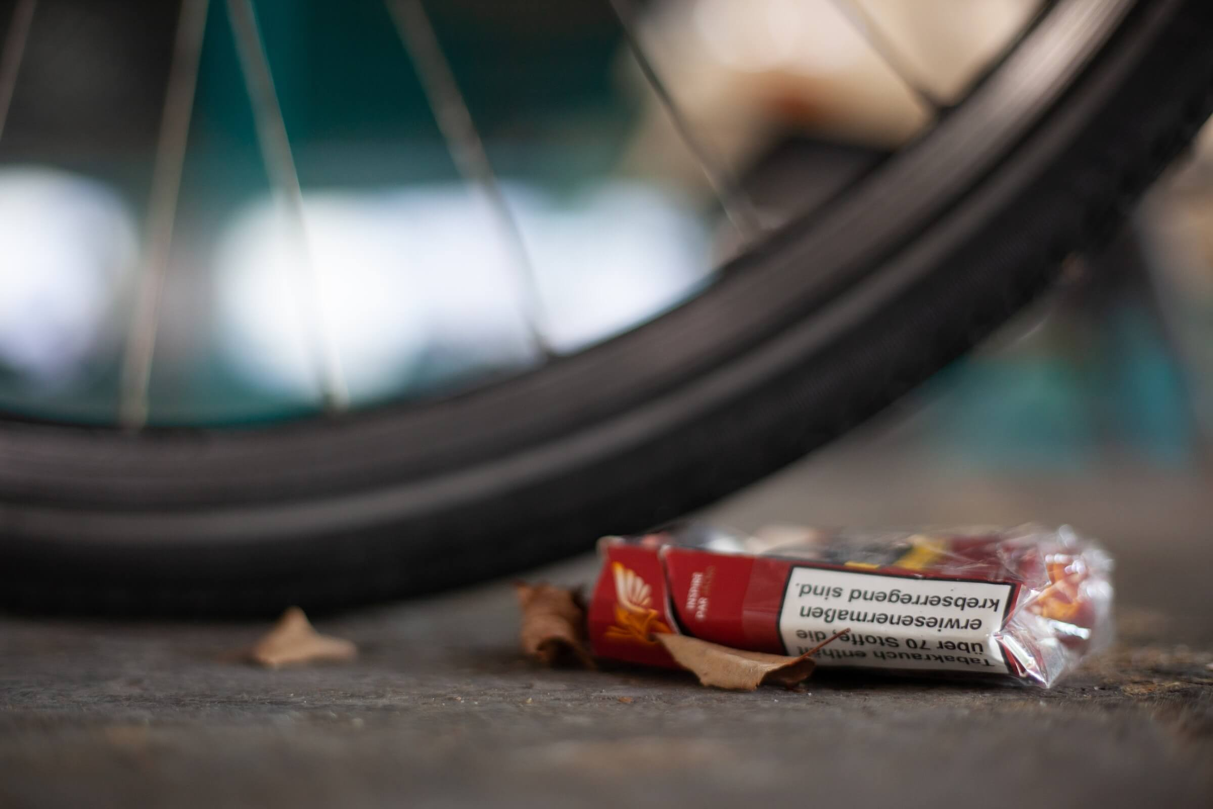 Box of cigarettes under a bicycle tire