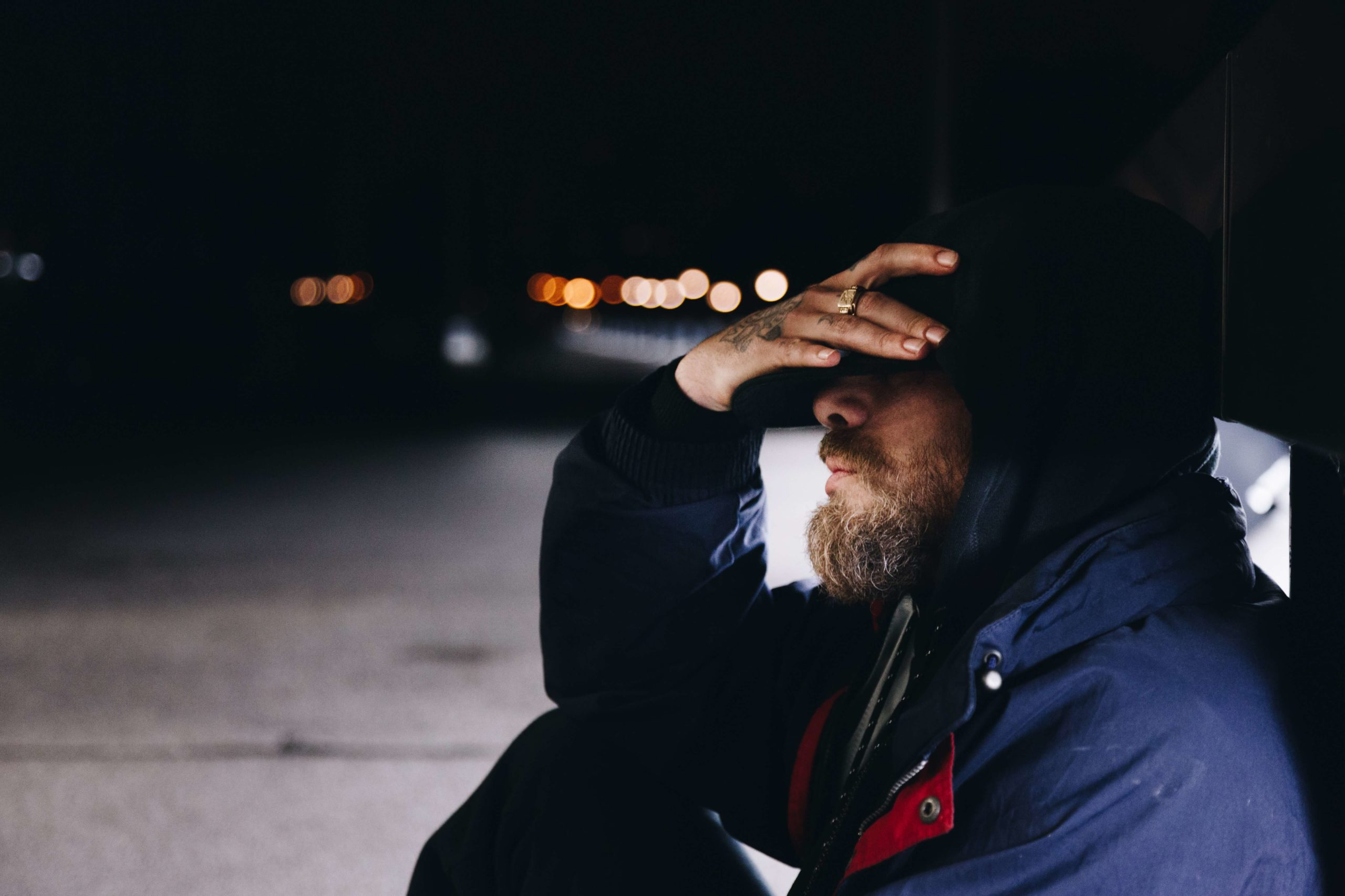 Homeless person covering his face