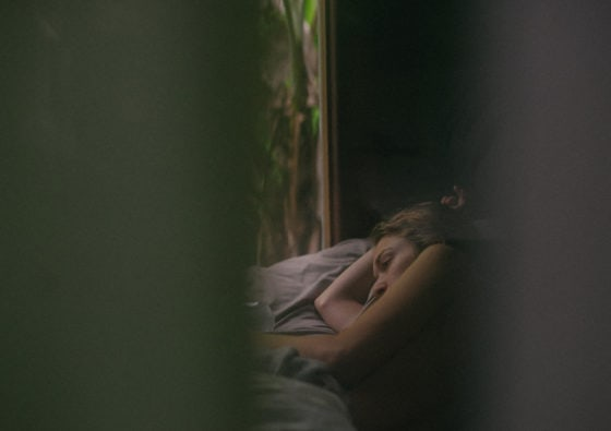 Woman lying in bed looking at the window
