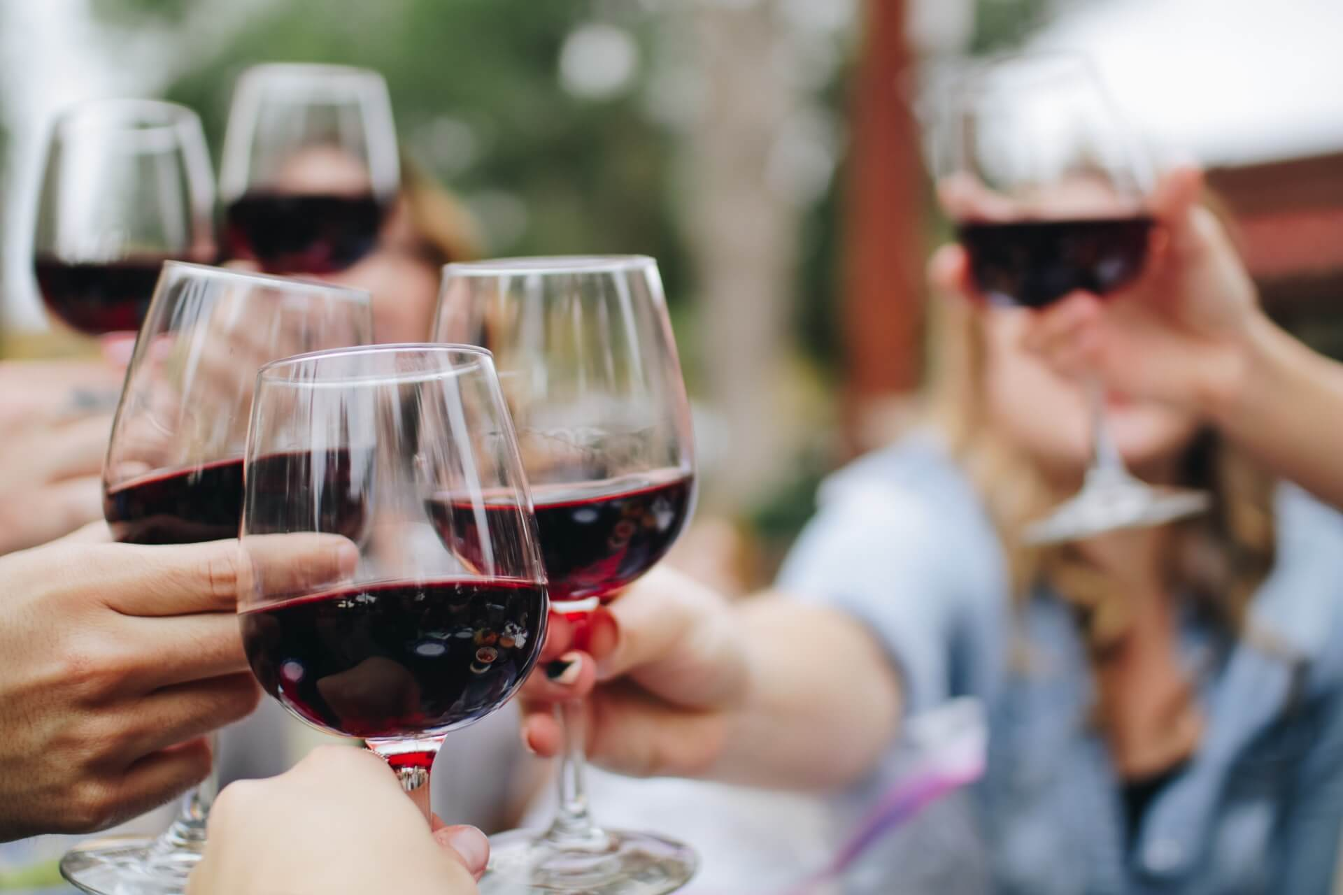 People drinking with wine in glasses