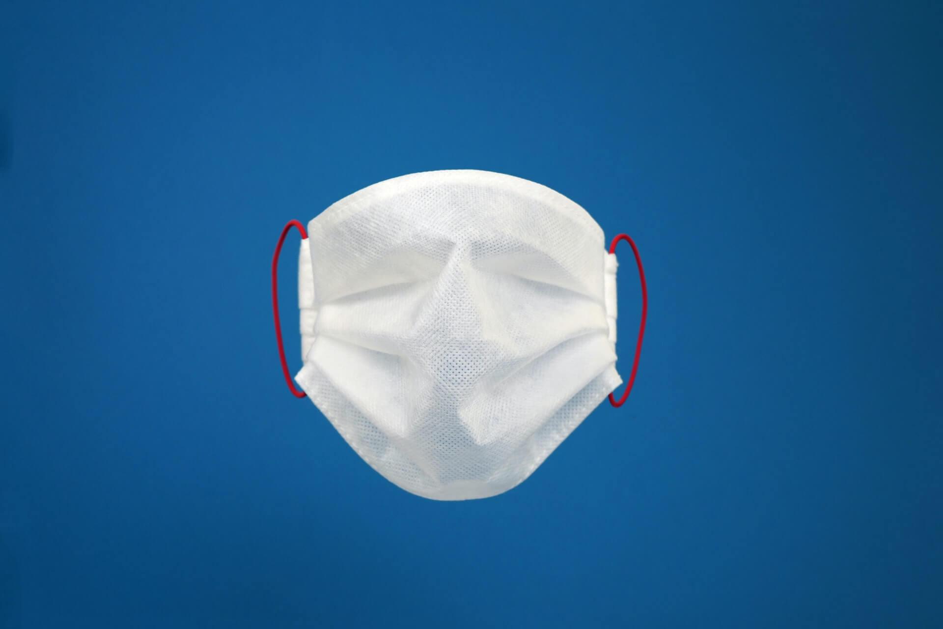 White face mask against blue background