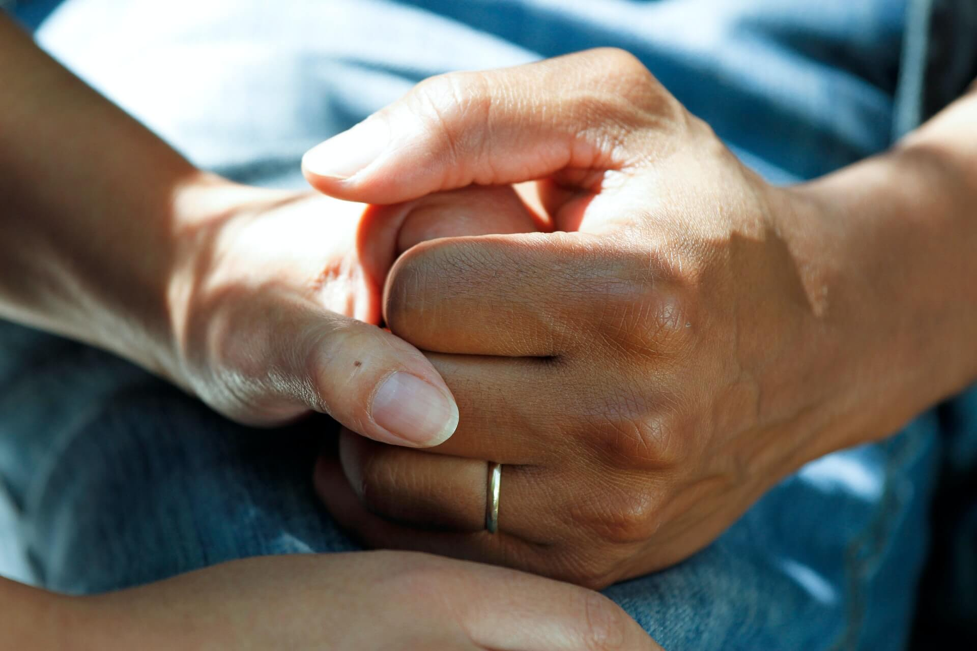 Patient with wedding ring holding hands with a loved one