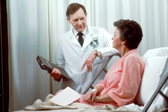 Doctor taking to a patient in bed